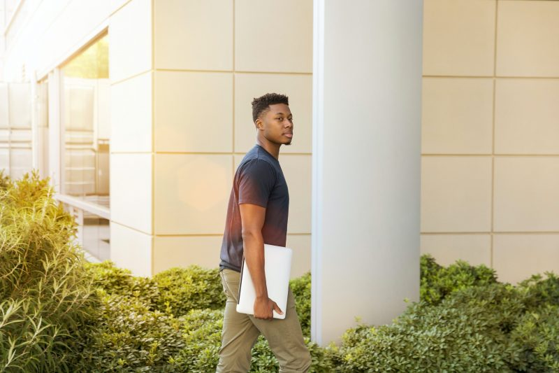 Young Black man carrying laptop into college building